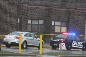 Two Antigo police department vehicles sit in front of the entrance to Antigo High School, Sunday, April 24, 2016, where an 18-year-old gunman opened fire late Saturday outside of a prom at the school. The shooter wounded two students before a police officer who was in the parking lot fatally shot him, authorities said Sunday. (Fred Berner/Antigo Daily Journal via AP) MANDATORY CREDIT