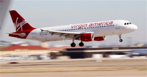 FILE - In this Dec. 1, 2010, file photo, Virgin America's inaugural flight between Los Angeles and Dallas Fort Worth International Airport comes in for a landing in Grapevine, Texas. Alaska Air Group Inc. is buying Virgin America in a deal worth more than $2 billion, creating a powerhouse airline with an expanded West Coast presence. Alaska Air said Monday, April 4, 2016, that the deal will expand its route network. (AP Photo/LM Otero, File)