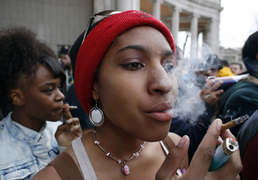 Destiny Sneed smokes marijuana during the annual 4/20 marijuana gathering at Civic Center Park in downtown Denver, Wednesday, April 20, 2016. Public consumption remains illegal under the state's recreational pot law, which was passed in 2012, but police mostly looked on as a cloud of marijuana smoke rose above the crowd. (AP Photo/Brennan Linsley)