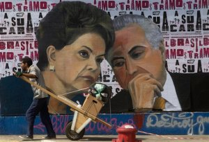 A man pushes a cart loaded with garbage for recycling in front of a mural depicting Brazil's President Dilma Rousseff and Vice President Michel Temer, in Sao Paulo, Brazil, Tuesday, April 19, 2016.  Temer who may become Brazil's next president is almost as unpopular as Rousseff, and stained by scandals of his own. He signed off on some of the allegedly illegal budget measures that led to the impeachment drive against Rousseff and has been implicated, though never charged, in several corruption investigations. (AP Photo/Andre Penner)
