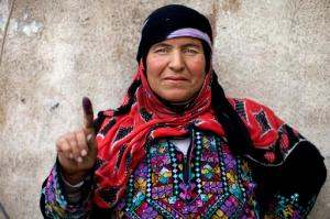 A Syrian woman poses for a photograph showing her inked finger after voting outside a polling station during the Syrian parliamentary election in Damascus, Syria, Wednesday, April 13, 2016. (AP Photo/Hassan Ammar)
