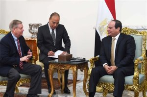 """In this photo provided by Egypt's state news agency, MENA, Egyptian President Abdel-Fattah el-Sissi, right meets with Republican Sen. Lindsey Graham, left, at the office of the Presidency in Cairo, Egypt. On Sunday, Graham told reporters in Cairo, that Republican candidate Donald Trump's campaign does not mean that the U.S. has """"fundamentally changed in terms of the way we view the world,"""" and even if he wins, the congress will be around doing its job. (MENA via AP) MANDATORY CREDIT"""