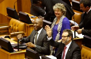 Mmusi Maimane, left, leader of the official opposition party in South Africa, the Democratic Alliance party, DA, react with other party members before a parliament session starts in Cape Town, South Africa, Tuesday, April 5,  2016.  A South African parliamentary debate over whether to remove President Jacob Zuma was delayed Tuesday after opposition lawmakers alleged that the parliament speaker Baleka Mbete, a Zuma ally, could not preside over the session because of alleged partiality.  (AP Photo/Schalk van Zuydam)