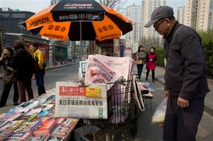 "A man looks at a newsstand with a copy of the day's Global Times displayed on a basket in Beijing, China, Tuesday, April 5, 2016. The nationalistic tabloid Global Times published an editorial saying an unidentified ""powerful force"" was behind the documents leaked from a Panama-based law firm that name relatives of current and retired Chinese politicians, including President Xi Jinping, as owning offshore companies. (AP Photo/Ng Han Guan)"