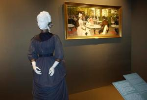 """In this photo taken on Tuesday, May 17, 2016, a Parisian haute couture walking dress from around 1884 is pictured alongside a period painting from the Uffizi Gallery's Galleria di Arte Moderna collection depicting the fashion of the era, on display at Pitti Palace in Florence, Italy, as part of the """"Across Art and Fashion'' series of exhibits at locations throughout Florence. The exhibit opened Thursday as Italy's Renaissance capital is reclaiming its centuries-old role as an incubator of the fashion-art dynamic.(AP Photo/Colleen Barry)"""
