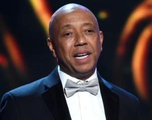 FILE - In this Feb. 6, 2015, file photo, hip-hop mogul Russell Simmons presents the Vanguard Award on stage at the 46th NAACP Image Awards in Pasadena, Calif. RushCard, the prepaid debit card company owned by Simmons, is agreeing to pay at least $19 million to compensate its users who were impacted by the company's multi-day outage in 2015. (Photo by Chris Pizzello/Invision/AP, File)