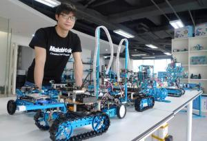 In this April 20, 2016 photo, Jasen Wang, founder of Shenzhen educational robot company Makeblock, poses with some of his company's products in Shenzhen, China. Once a collection of fishing enclaves next door to Hong Kong, Shenzhen has become the epicenter of China's manufacturing-driven miracle is staking its future growth on finance, technology and culture. (AP Photo/Kelvin Chan)