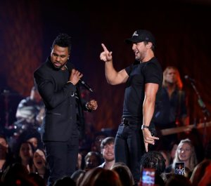 "FILE - In this March 29, 2016 file photo, Jason Derulo, left, and Luke Bryan perform during a taping of CMT Crossroads in Franklin, Tenn. During an interview prior to shooting the episode, Derulo, the ""Talk Dirty"" singer, said he is really interested in making a country music record. (Photo by Donn Jones/Invision/AP, File)"