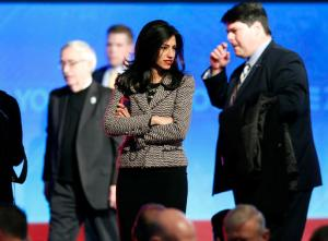 In this photo taken Dec. 19, 2015, Huma Abedin, center, aide to Hillary Clinton, stands on stage after a Democratic presidential primary debate in Manchester, N.H. FBI agents probing whether Hillary Clinton's use of a private email server imperiled government secrets appear close to completing their work, a process experts say will likely culminate in a sit-down with the former secretary of state.  (AP Photo/Jim Cole)