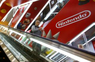 FILE - In this March 20, 2016 file photo, a shopper on an escalator passes by the Nintendo logo at an electronics store in Tokyo. Japanese video game maker Nintendo Co., which makes the Wii U home console and Nintendo 3DS hand-held machine, is eyeing the movie business for growth. Company spokesman Makoto Wakae said Monday, May 16 details are undecided but the work might be a theater release or a DVD. (AP Photo/Shizuo Kambayashi, File)