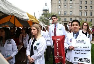 Medical students from Southern Illinois University School of Medicine listen to speakers during a rally supporting increased funding to education held near the state Capitol complex in Springfield on Wednesday, April 20, 2016. The rally, themed Save Higher Education: No Future Without Funding, was sponsored by the Illinois Coalition to Invest in Higher Education, and was attended by hundreds of other college students from throughout the state. (David Spencer/The State Journal-Register via AP) NO SALES, MANDATORY CREDIT