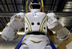 """In this May 2, 2016 photo, a six-foot-tall, 300-pound Valkyrie robot is seen at University of Massachusetts-Lowell's robotics center in Lowell, Mass. """"Val,"""" one of four sister robots built by NASA, could be the vanguard for the colonization of Mars by helping to set up a habitat for future human explorers. But first they're finding new homes on Earth and engineers to hone their skills. (AP Photo/Elise Amendola)"""