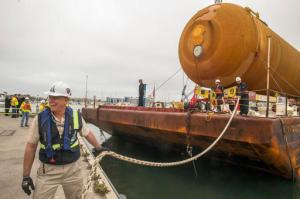Dennis Jenkins, Project Director Samuel Oschin Air and Space Center at the California Science Center Foundation pulls a line as the space shuttle external propellant tank ET- 94, arrives aboard a barge at Marina del Rey, Calif., on Wednesday, May 18, 2016. NASA's only remaining version of the tank will be placed on dollies and pulled by a truck to its final destination near the California Science Center's Samuel Oschin Pavilion in Los Angeles. (AP Photo/Damian Dovarganes)