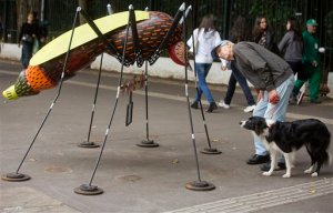 A man walking his dog, stops to examine an Aedes aegypti mosquito sculpture created by street artist Andre Farkas, on a Paulista Ave. sidewalk, in Sao Paulo, Brazil, Friday, May 27, 2016. According to Farkas, the sculpture is intended to bring awareness to the spread of the Zika virus in Brazil. (AP Photo/Andre Penner)