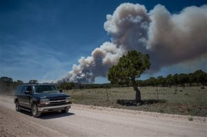 "Residents of the town of Chilili along state road 337 begin to evacuate due to the Dog Head wildfire near the Manzano mountains, Wednesday, June 15, 2016, in Chilili, N.M. Authorities don't have a containment estimate yet for a wildfire burning in the Manzano Mountains southeast of Albuquerque but say good weather helped firefighters attack the fire overnight. The so-called ""Dog Head Fire"" in part of the Cibola National Forest east of Los Lunas started Tuesday and grew to over a square mile by Wednesday morning after its growth slowed overnight. (Roberto E. Rosales/The Albuquerque Journal via AP) MANDATORY CREDIT"