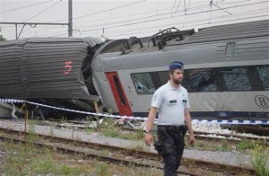 A police officer walks by the wreckage of a passenger and freight train after they collided in Hermalle-sous-Huy, near Liege, Belgium on Monday, June 6, 2016. Belgian media reported several dead and injured as a passenger train struck a freight train. (AP Photo/Virginia Mayo)