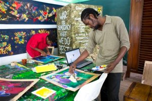 In this May 28, 2016 photo, art student Rubens Corneille, right, prepares his work during the Mixed Media class with Tessa Mars at the resurrected Centre d'Art or Art Center, in Port-au-Prince, Haiti. The Haitian nonprofit Knowledge & Freedom Foundation and a French family foundation are the main providers of institutional support for the Centre d'Art. (AP Photo/Dieu Nalio Chery)