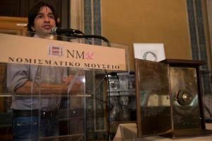 Yanis Bitsakis speaks behind a possible reconstruction of the more than 2,000-year-old Antikythera Mechanism during a press conference in Athens, Thursday, June 9 , 2016. An international team of scientists says a decade's painstaking work on the corroded fragments found in an ancient Greek shipwreck has deciphered roughly 500 words of text that explained the workings of the complex machine, described as the world;s first mechanical computer. (AP Photo/Petros Giannakouris)