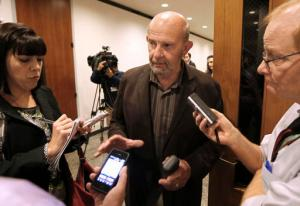 FILE - In this Nov. 8, 2013 file photo, John Tos, a Hanford farmer and the lead plaintiff in a lawsuit to block the sale of bonds to build California's bullet train, talks with reporters after a hearing in the case in Sacramento County Superior Court in Sacramento, Calif. Kings County Counsel Colleen Carlson said Thursday, May 26, 2016, that the county board of supervisors has voted against appealing the judge's ruling that allowed planning and financing of the California high-speed rail project to proceed. (AP Photo/Rich Pedroncelli, File)