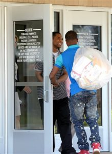 With his brother Deshon carrying his bag, Davontae Sanford, 23, smiles as he takes his first steps outside of the Bellamy Creek Correctional Facility, Wednesday, June 8, 2016, in Ionia, Mich. Sanford entered prison as a teenager in 2008 and was released Wednesday, a day after his guilty pleas to four fatal shootings were erased by a judge at the request of prosecutors who conceded the case was compromised by flawed police work. (Dave Wasinger/Lansing State Journal via AP)  NO SALES; MANDATORY CREDIT