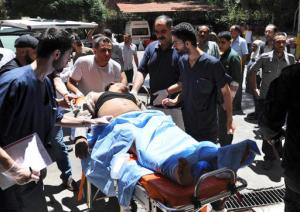 In this photo released by the Syrian official news agency SANA, shows a victim who was injured in the bombing attack in the Sayyida Zeinab suburb carried on a stretcher into a hospital in Damascus, Syria, Saturday, June 11, 2016. Two bombs went off Saturday near the Syrian capital, killing at least eight people and wounding over a dozen others in the latest attack to hit the predominantly Shiite area in recent months, state TV and an opposition activist group said. (SANA via AP)