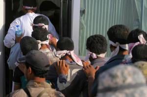 Blindfolded men are led to a bus after being detained during fighting between Iraqi security forces and Islamic State militants during a military operation to regain control of Fallujah, 40 miles (65 kilometers) west of Baghdad, Iraq, Wednesday, June 1, 2016. Since the operation began, the United Nations says they have received reports that some 500 men and boys have been detained for questioning as thousands of civilians have fled the city's mostly rural outskirts.(AP Photo/Anmar Khalil)