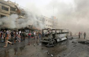 Civilians gather at the scene of a deadly suicide car bomb attack in the neighborhood of New Baghdad, Iraq, Thursday, June 9, 2016. Two separate suicide attacks in and outside the Iraqi capital have killed at least 27 people and wounded dozens. Officials say the deadliest bombing took place in New Baghdad, a commercial area of a majority Shiite neighborhood, killing over a dozen civilians. Another suicide bomber rammed his explosives-laden car into an Iraqi army checkpoint north of Baghdad, killing at least 12 people. (AP Photo/Hadi Mizban)