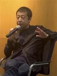In this Saturday, June 18, 2016 photo, Chinese director Jia Zhangke speaks at an event in Beijing. Jia says he will make a virtual reality film with a romantic story next year as he and viewers get used to the new medium. (AP Photo/Louise Watt)