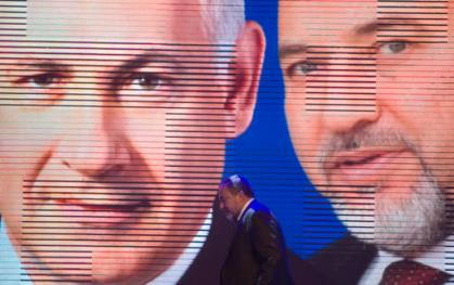 FILE - In this Tuesday, Dec. 25, 2012, file photo, Israeli Foreign Minister Avigdor Lieberman walks under a screen showing him and Israeli Prime Minister Benjamin Netanyahu during the inauguration of their election campaign in Jerusalem. Israel's incoming defense minister once called for bombing Egypt, just weeks ago suggested that Israel kill Hamas' leader in the Gaza Strip and has opposed prosecution of a soldier accused of manslaughter _ just a few of the positions that could put former bar bouncer Avigdor Lieberman at odds with a military he now commands. (AP Photo/Dan Balilty, File)