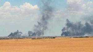 This Wednesday June 8, 2016 video grab shows smoke rising from the city of Manbij, Syria. U.S.-backed fighters on Thursday closed all major roads leading to the northern Syrian town of Manbij, a stronghold of the Islamic State group, and surrounded it from three sides, officials and Syrian opposition activists said. The town is one of the largest areas held by IS in the northern Aleppo province. (ARAB 24 via AP)