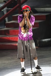 FILE - In this Sept. 1, 2013 file photo, Lil Wayne (AKA Dwayne Michael Carter, Jr.) performs as a part of the America's Most Wanted Tour at the Verizon Wireless Amphitheater in Irvine, Calif. Lil Wayne is in stable condition in Omaha, Neb. after suffering what his publicist described Tuesday, June 14, 2016, as two minor seizures. TMZ has reported that the Grammy-winning rapper's private jet was forced to make two emergency landings at an Omaha airport Monday afternoon, June 13, and that he was taken to a hospital. (Photo by Paul A. Hebert/Invision/AP, File)