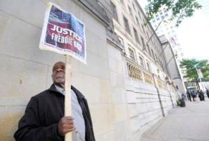 FILE- In this June 9, 2016 file photo, Arthur B. Johnson Jr., of Baltimore, demonstrates alone outside Baltimore's Courthouse East on the first day of the trial of Officer Caesar Goodson, one of six Baltimore city police officers charged in connection to the death of Freddie Gray, in Baltimore. More than a year after Freddie Gray's death, the same streets that exploded in fury and flame are calm. Despite back-to-back acquittals for officers charged in Gray's death, the physical protest movement that helped topple the careers of both the police commissioner and the mayor has dissipated, leaving activists exploring other avenues for change. (AP Photo/Steve Ruark, File)