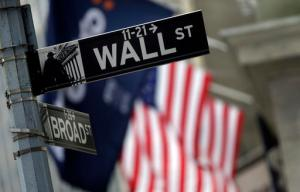 FILE - This Thursday, Oct. 2, 2014, file photo, shows a Wall Street sign adjacent to the New York Stock Exchange. Global stocks were mixed in listless trading Wednesday, Aug. 31, 2016, ahead of key U.S. jobs data later in the week that could help determine how soon the Federal Reserve raises interest rates. (AP Photo/Richard Drew, File)