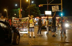 People protest and block traffic in Milwaukee, Sunday, Aug. 14, 2016.Police said one person was shot at a Milwaukee protest on Sunday evening and officers used an armored vehicle to retrieve the injured victim during a second night of unrest over the police shooting of a black man, but there was no repeat of widespread destruction of property.  (AP Photo/Jeffrey Phelps)