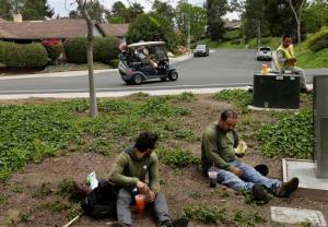FILE - In this May 4, 2016, file photo, Duncan Wallace drives a golf cart from his house to his golf club as a group of landscape workers take a break in Vista, Calif. Income inequality has surged near levels last seen before the Great Depression. The average income for the top 1 percent of households climbed 7.7 percent last year to $1.36 million, according to tax data. That privileged sliver of the population saw pay climb at almost twice the rate of income growth for the other 99 percent, whose pay averaged a humble $48,768. (AP Photo/Gregory Bull, File)