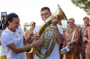 In this photo taken on Sunday, Aug. 28, 2016, women's pole vault world record holder, Yelena Isinbayeva, left, jokes with a military musicians as she visits the Hemeimeem air base in Syria. Russian athletes including the women's pole vault world record holder, Yelena Isinbayeva, have visited an air base in Syria that Russia uses to target Islamic State fighters.(Olga Balashova/Russian Defense Ministry Press Service pool photo via AP)