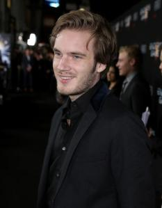 """FILE - In this Oct. 28, 2013 file photo, Felix """"PewDiePie"""" Kjellberg's arrives at the Los Angeles premiere of """"Ender's Game"""" at TCL Chinese Theatre in Los Angeles. Kjellberg's Twitter account was briefly suspended this week and the blue check mark detonating his once-verified status was removed after the YouTube star changed his avatar. He said in a video posted Wednesday, Aug. 31, 2016, on YouTube that he purposely unverified his account """"as a joke"""". (Photo by Matt Sayles/Invision/AP, File)"""