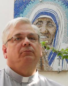 """Rev. Brian Kolodiejchuk, postulator of the cause of beatification and canonization of Mother Teresa, is interviewed by the Associated Press in front of a mosaic picturing Mother Teresa, at the formation house of the priestly branch of the Missionaries of Charity on the outskirts of Rome, Friday, Aug. 18, 2016. When Pope Francis canonizes Mother Teresa on Sunday, Sept. 4, 2016, he'll be honoring a nun who won admirers around the world and a Nobel Peace Prize for her joy-filled dedication to the """"poorest of the poor."""" (AP Photo/Giulia Sabella)"""