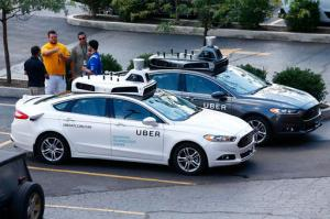 People stand by self-driving Ford Fusion hybrid cars while test driving the vehicles, Thursday, Aug. 18, 2016, in Pittsburgh. Uber said that passengers in Pittsburgh will be able to summon rides in self-driving cars with the touch of a smartphone button in the next several weeks. The high-tech ride-hailing company said that an unspecified number of autonomous Ford Fusions with human backup drivers will pick up passengers just like normal Uber vehicles. Riders will be able to opt in if they want a self-driving car, and rides will be free to those willing to do it, spokesman Matt Kallman said. (AP Photo/Jared Wickerham)