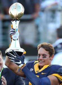 California Golden Bears' Chad Hansen holds the trophy presented to his team after defeating the Hawaii Rainbow Warriors in the opening game of the U.S. college football season at Sydney's Olympic stadium in Sydney, Saturday, Aug. 27, 2016. The last American football of any kind played in Sydney was an NFL preseason game at the Olympic stadium that attracted 73,000 spectators in 1999. (AP Photo/Rick Rycroft)
