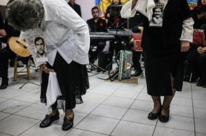 In this Sept. 5, 2016 photo, Violeta Zuniga, right, and Martha Perez, wearing photographs of their respective partners who were disappeared during Gen. Augusto Pinochet's 1973-1990 rule and holding handkerchiefs, perform Chile's national dance the cueca at a school in Santiago, Chile. The courtship dance was first performed alone in public in 1978 to commemorate International Women's Day. The handkerchief, which is traditionally used in the cueca, has become a symbol of mourning for the women who continue to search for their disappeared loved ones. (AP Photo/Esteban Felix)