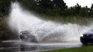 Traffic speeds through floodwaters along Military Highway in Chesapeake, Va. Wednesday, Sept. 21, 2016. A stalled weather system and the remnants of Tropical Storm Julia have brought days of rain and localized flooding to the region through Wednesday. (Steve Earley/The Virginian-Pilot via AP)
