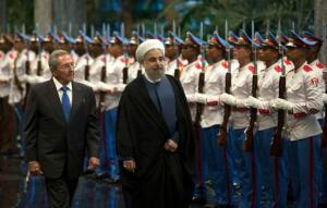Cuba's President Raul Castro, left, escorts Iranian President Hassan Rouhani, center, as they inspect the honor guard at Revolution Palace in Havana, Cuba, Monday, Sept 19, 2016. Rouhani is on a one-day official visit to Cuba. (Ismael Francisco, Cubadebate via AP)