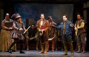 """This image released by Boneau/Bryan-Brown shows Edward Hibbert, foreground from left, Josh Grisetti and Rob McClure and the cast during a performance of """"Something Rotten,""""  in New York. Producer Kevin McCollum said Thursday the show will end its run Jan. 1 after 742 total shows. A national tour is planned to kick off in Boston on Jan. 17 and McCollum said he's in talks for potential productions in Japan and London. (Joan Marcus/Boneau/Bryan-Brown via AP)"""