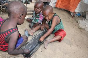Children play on the ground outside their makeshift home in a refugee camp in Mogadishu, Somalia, Tuesday,Sept,20, 2016. A new U.N. report says five million people in Somalia are not getting enough food. That's more than 40 percent of the population of this chaotic Horn of Africa country. The report released Tuesday says the number of people who are food insecure has increased by 300,000 since February. The report says more than 300,000 children under 5 are acutely malnourished. (AP Photo/Farah Abdi Warsameh)