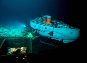 """The Pisces IV submersible sits atop the summit of Cook seamount, as seen from the Pisces V craft, during a dive to the previously unexplored underwater volcano off the coast of Hawaii's Big Island on Sept. 6, 2016. """"We don't know anything about the ocean floor,"""" said Peter Seligmann, chairman, CEO and co-founder of Conservation International. """"What we know is that each one of those seamounts is a refuge for new species, but we don't know what they are. We don't know how they've evolved. We don't know what lessons they have for us."""" (AP Photo/Caleb Jones)"""