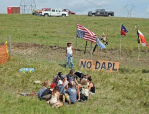 Bill Left Hand, of McLaughlin, South Dakota, stands next to a sign at the site of a protest Friday, Aug. 12, 2016, against construction of the Dakota Access Pipeline that will cross the Missouri River in Morton County. The pipeline would start in North Dakota and pass through South Dakota and Iowa before ending in Illinois. Construction of the pipeline began this week just north of the Standing Rock Sioux reservation. Nearly 200 people came from across the country to join in the protest. (Tom Stromme/The Bismarck Tribune via AP)