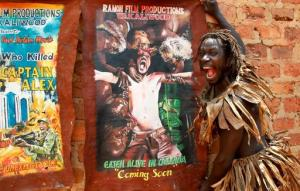 """In this photo taken Wednesday, Sept. 7, 2016, actor Francis Kagoro pulls a face for the camera while showing posters of previous movies, at the """"Wakaliwood"""" studios in the Wakaliga slum of Kampala, Uganda. Deep in this Kampala slum at a tin-roofed collection of houses known as Wakaliwood, is the engine of Uganda's tiny film industry and the source of $200-budget movies and a glimmer of fame. (AP Photo/Stephen Wandera)"""