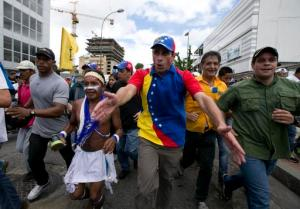 "FILE - In this Sept 1, 2016 file photo, Venezuelan opposition leader Henrique Capriles takes part in the ""taking of Caracas"" march in Caracas, Venezuela. Capriles says he was harassed in a Margarita island airport for four hours by armed and hooded government supporters. The tense standoff ended after midnight Wednesday, Sept. 7,  when the supporters withdrew from an area close to baggage claim where they awaited Capriles.   (AP Photo/Ariana Cubillos, File)"