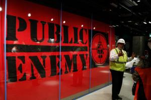 In this photo taken July 18, 2016, Museum Director Lonnie Bunch stands in-front of an art piece representing hip-hop group Public Enemy in the Smithsonian National Museum of African American History and Culture in Washington, during a media tour. The museum's grand opening will be on Sept. 24. (AP Photo/Paul Holston)